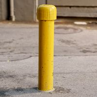 Yellow freshly painted parking post (bollard)